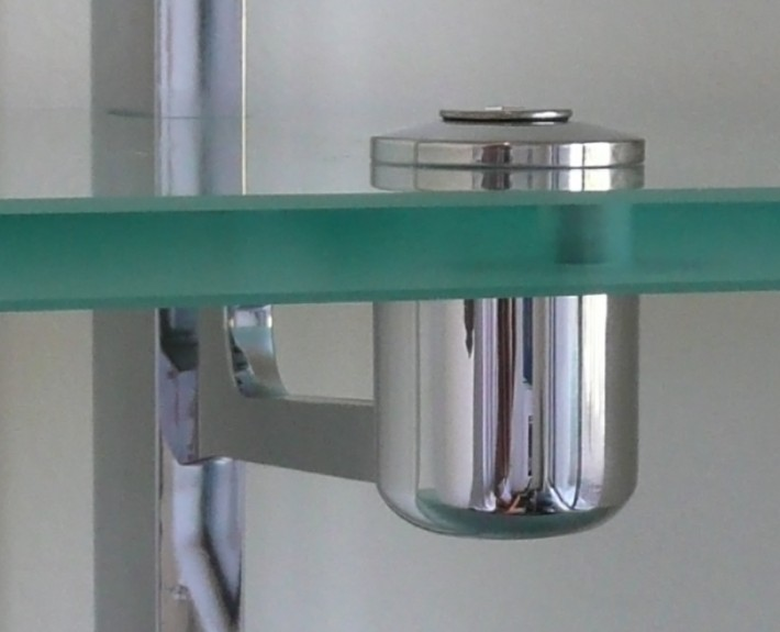 Stainless steel bracket set into glass shelving unit